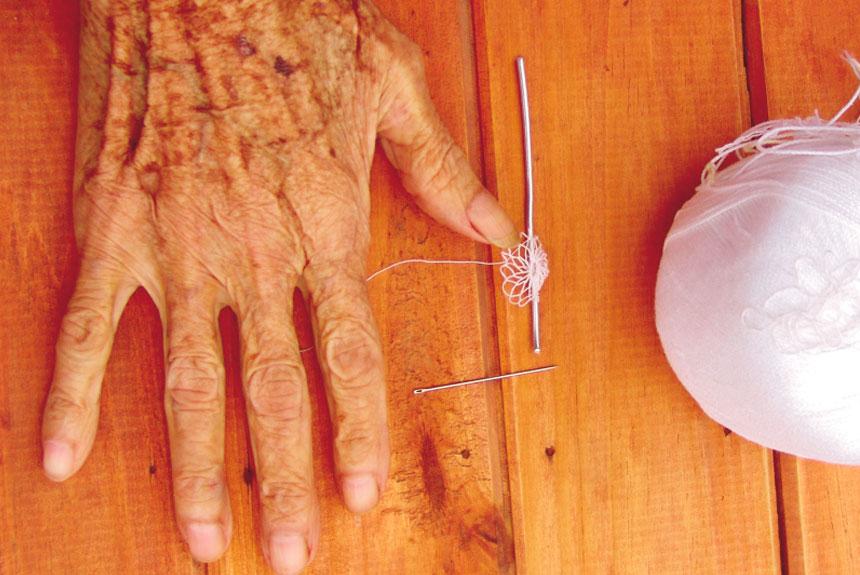 Mano de mujer sobre mesa con aguja y ovillo